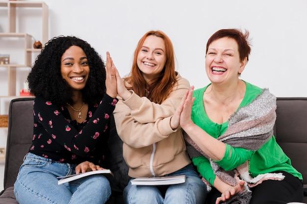 Grupo de mulheres posando juntos, segurando livros