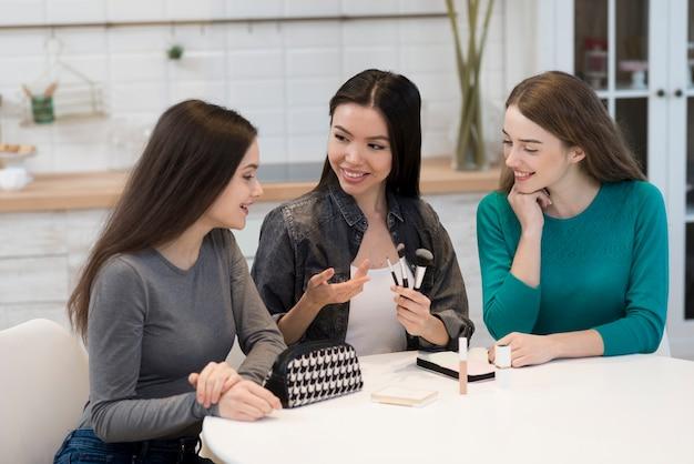 Grupo de mulheres positivas, tentando acessórios de maquiagem