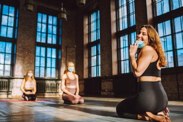 Grupo de mulheres praticando ioga em classe de estilo loft grande usando máscaras médicas protetoras. pandemia, conceito de distância social.