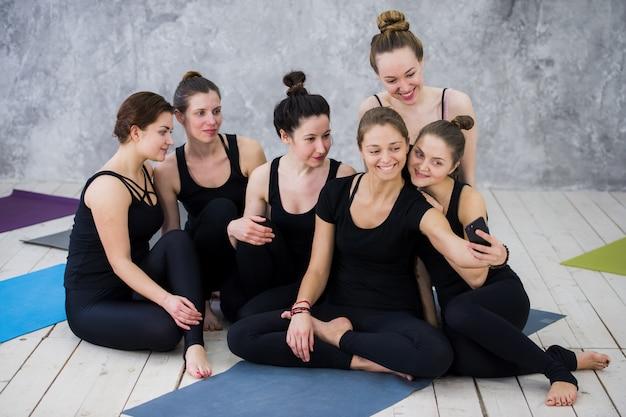 Grupo de mulheres sentadas e relaxando depois de uma longa aula de ioga e tomando selfie