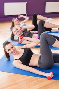 Grupo de mulheres sorridentes ativas estão treinando no clube de fitness.