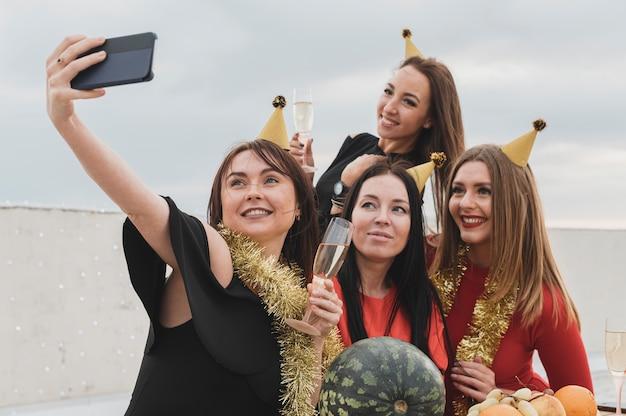 Grupo de mulheres sorridentes tomando uma selfie de grupo