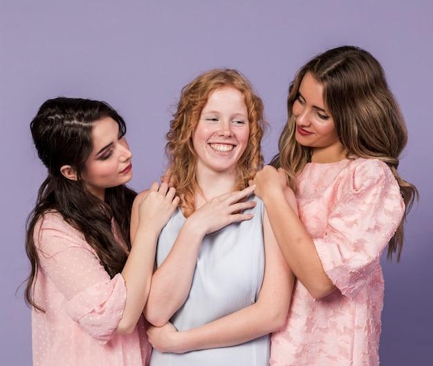 Grupo de mulheres sorrindo e posando, segurando um ao outro