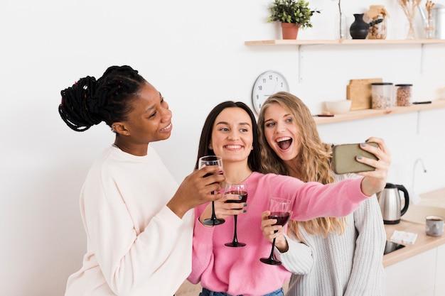 Grupo de mulheres tomando uma selfie com um copo de vinho