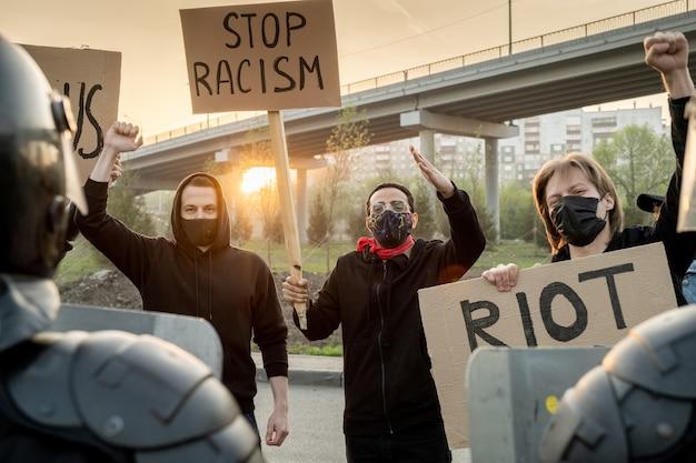 Grupo de multidão insatisfeita com máscaras levantando os punhos e gritando enquanto afirmam parar o racismo ao ar livre