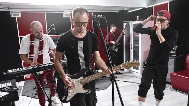 Grupo de música moderna na base de ensaio, gravando álbum de faixas