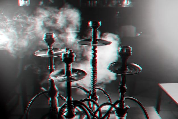 Grupo de narguilés no interior de uma sala de narguilé com fumaça