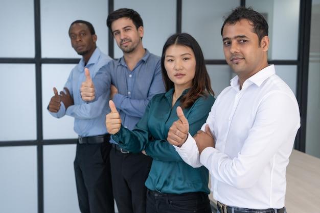 Grupo de negócio multirracial que levanta na sala de reunião.