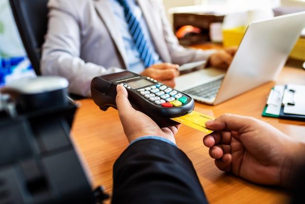 Grupo de negócio que guarda o cartão de crédito com sistema de pagamento de nfc no escritório moderno.