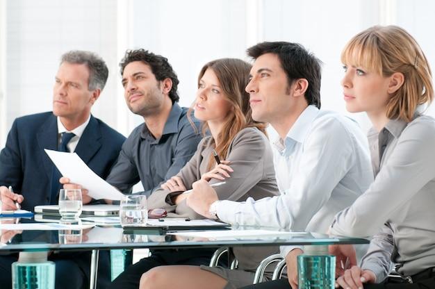 Grupo de negócios de pessoas presentes e ouvindo na conferência