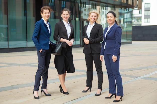 Grupo de negócios feminino de sucesso feliz juntos perto de prédio de escritórios, posando, olhando para a câmera e sorrindo. comprimento total, vista frontal. conceito de retrato de grupo de mulheres de negócios