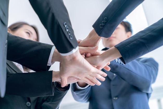 Grupo de oficial trabalho de equipe está feliz e une mãos para celebrar em sucesso