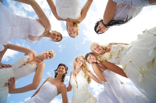 Grupo de oito noivas felizes juntos ao ar livre com um céu azul ao fundo