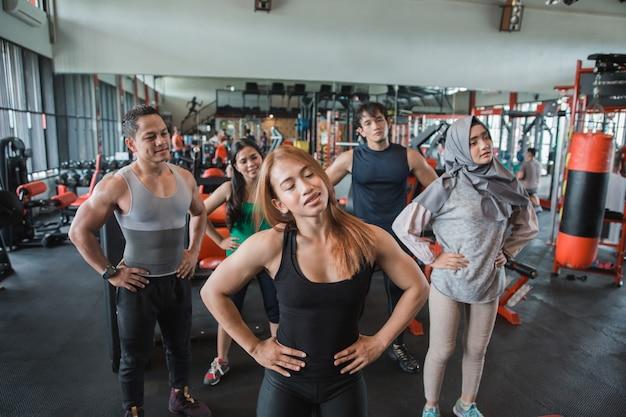 Grupo de olhar frontal de pessoas na academia, estendendo-se para aquecer