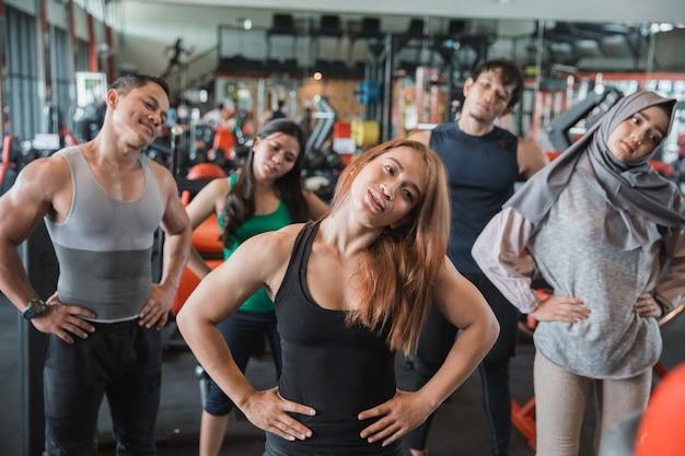 Grupo de olhar frontal de pessoas no centro de fitness, estendendo-se para w