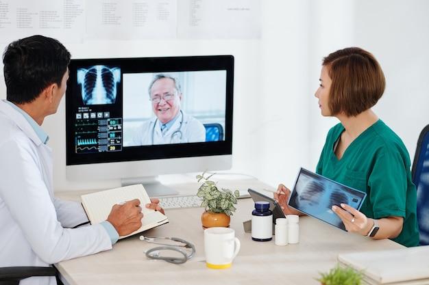 Grupo de oncologistas discutindo caso difícil em reunião online