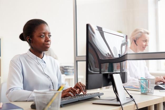 Grupo de operadoras de call center usando computadores no local de trabalho, foco em jovem afro-americana usando fone de ouvido em primeiro plano
