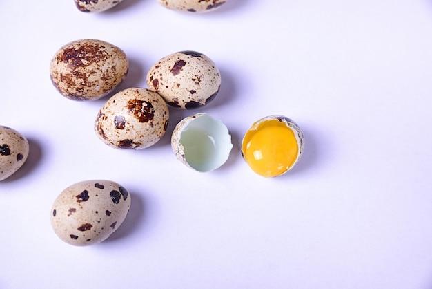 Grupo de ovos de codorna e um ovo quebrado com gema