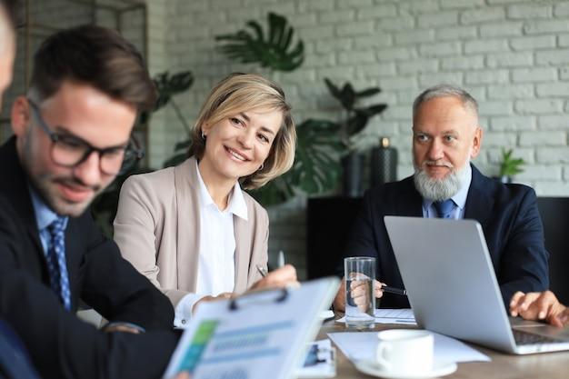 Grupo de parceiros de negócios, discutindo ideias e planejando o trabalho no escritório.