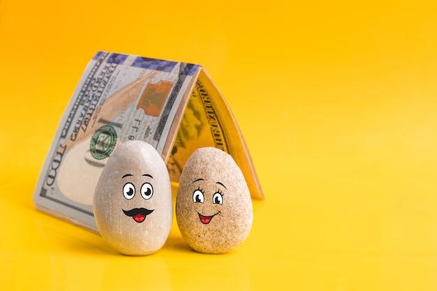 Grupo de pedras com caretas engraçadas desenhadas e uma casa feita de dinheiro. casal de namorados tem um bom plano financeiro. investimento, depósito bancário, conceito de gestão de dinheiro.