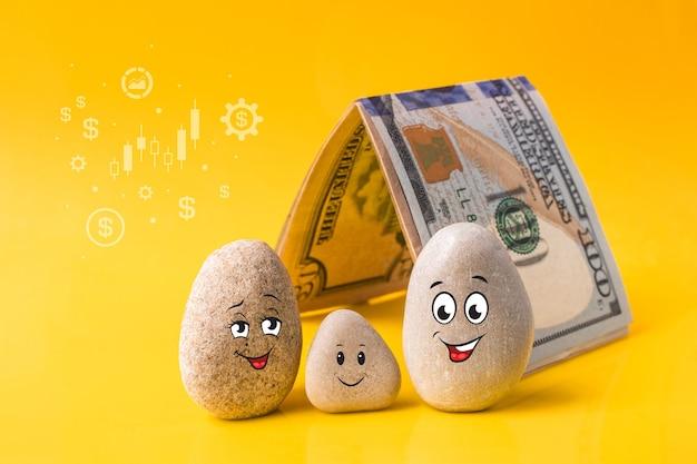 Grupo de pedras com caretas engraçadas desenhadas e uma casa feita de dinheiro. pai, mãe e filho deles. família com bom plano financeiro. investimento, depósito bancário, conceito de gestão de dinheiro.