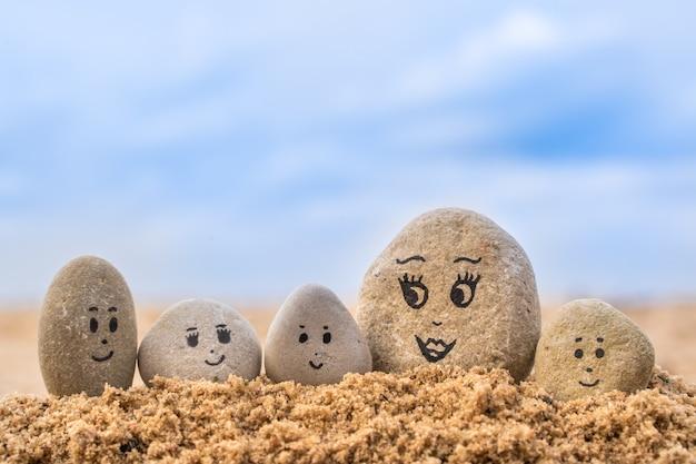 Grupo de pedras com rostos desenhados na areia. mãe e seus filhos. cartão de conceito de feliz dia das mães.