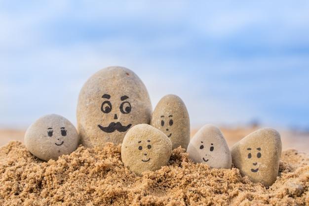 Grupo de pedras com rostos desenhados na areia. pai e seus filhos. feliz dia dos pais cartão do conceito.