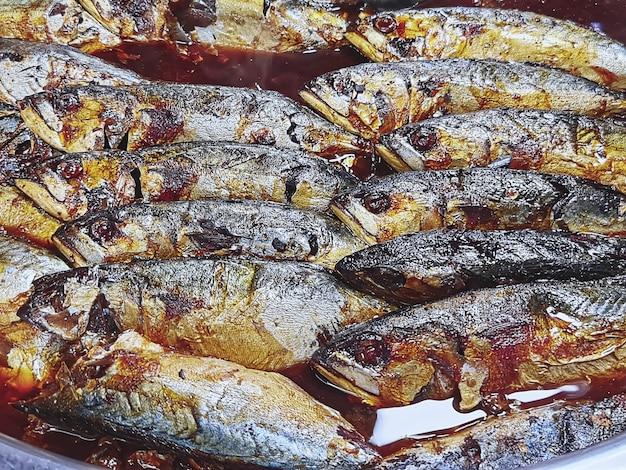 Grupo de peixes de cavala adoçados cozidos em uma tigela grande de aço inoxidável Foto Premium