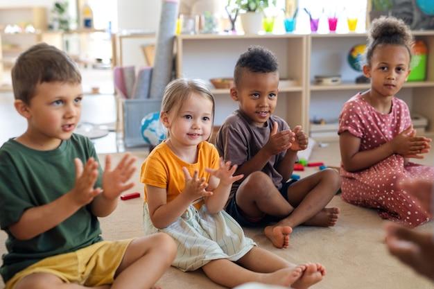 Grupo de pequenas crianças da creche, sentadas no chão dentro da sala de aula, batendo palmas