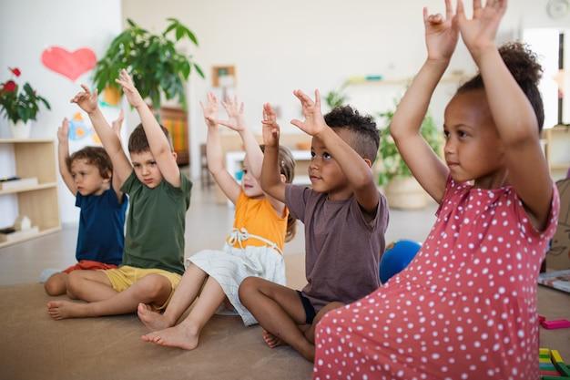 Grupo de pequenas crianças da creche sentadas no chão dentro da sala de aula brincando