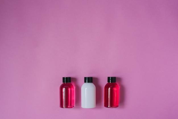 Grupo de pequenas garrafas de viagem para cuidados com o corpo: gel de banho, shampoo, bálsamo, loção no fundo rosa. a composição da camada plana de cosméticos copie o espaço.