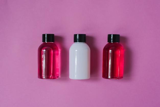 Grupo de pequenas garrafas de viagem para cuidados com o corpo: gel de banho, shampoo, bálsamo, loção no fundo rosa. a composição da camada plana de cosméticos