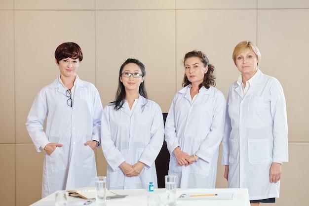 Grupo de pesquisas femininas positivas em jalecos de pé à mesa após a conformidade com a nova vacina contra o coronavírus