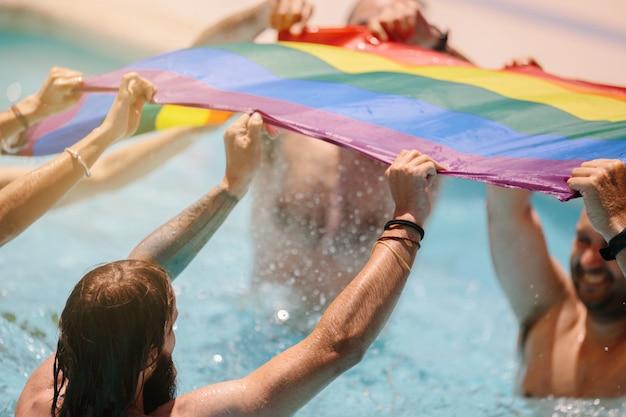 Grupo de pessoas acenando uma bandeira lgtb dentro de uma piscina