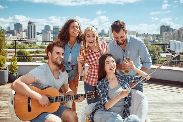 Grupo de pessoas alegres e jovens com violão fazendo selfie e sorrindo
