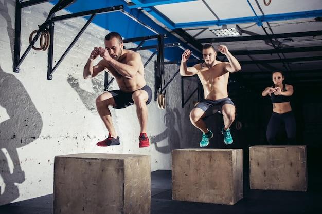 Grupo de pessoas atléticas pulando sobre algumas caixas em uma academia de cross-training