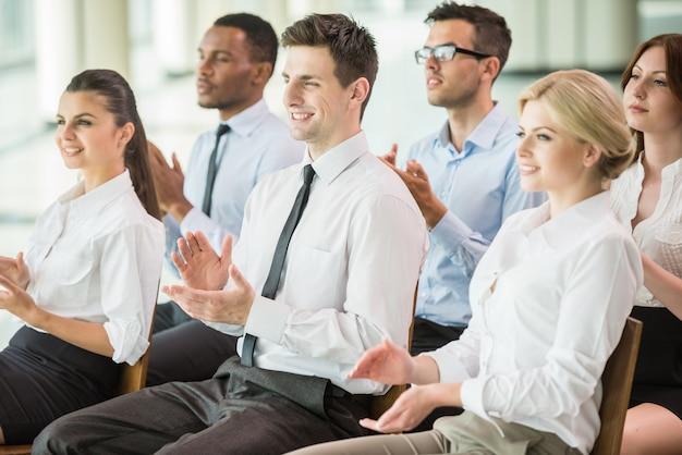Grupo de pessoas batendo palmas de mãos durante uma conferência de reunião.