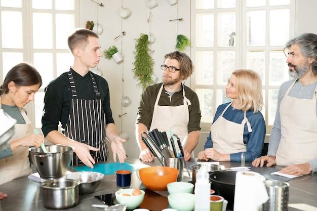 Grupo de pessoas com avental olhando para o treinador de culinária masculino e ouvindo-o durante a aula magna enquanto estão em pé ao redor da grande mesa da cozinha
