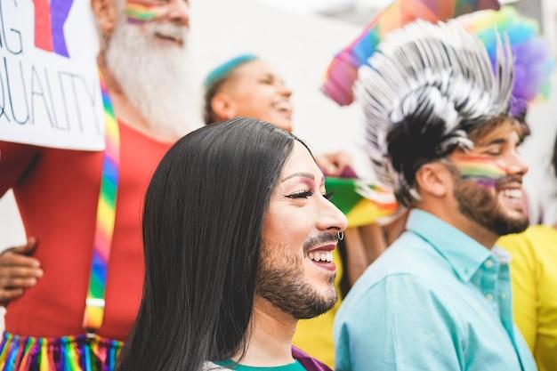 Grupo de pessoas com bandeiras e faixas de arco-íris durante o evento do orgulho gay