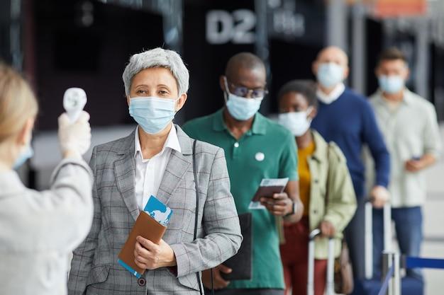 Grupo de pessoas com máscara em pé em uma fileira e testando se estão no aeroporto