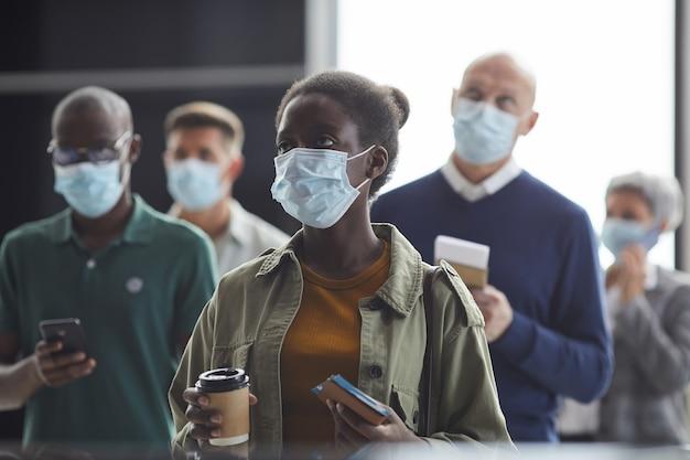 Grupo de pessoas com máscaras protetoras segurando ingressos e esperando a partida no aeroporto