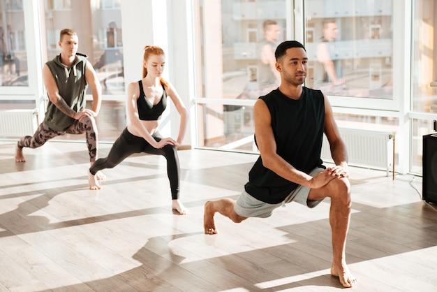 Grupo de pessoas com os pés descalços, fazendo exercícios de ioga em estúdio
