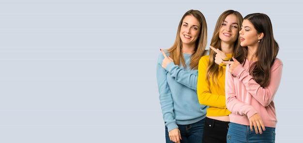 Grupo de pessoas com roupas coloridas, apontando para o lado para apresentar um produto