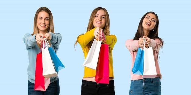 Grupo de pessoas com roupas coloridas, segurando um monte de sacolas de compras em background colorido