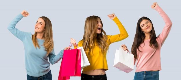 Grupo de pessoas com roupas coloridas, segurando um monte de sacos de compras