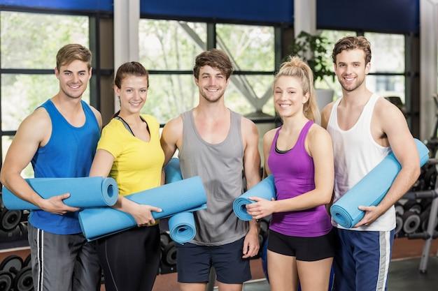 Grupo de pessoas com tapete de fitness no ginásio