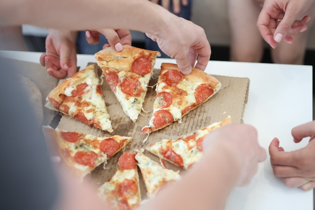 Grupo de pessoas comendo fatias de pizza
