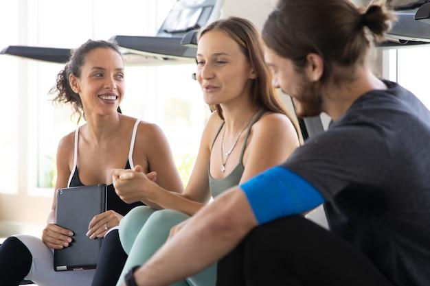 Grupo de pessoas conversando e rindo felizes juntos após o treino no ginásio. estilo de vida saudável e conceitos de esporte.