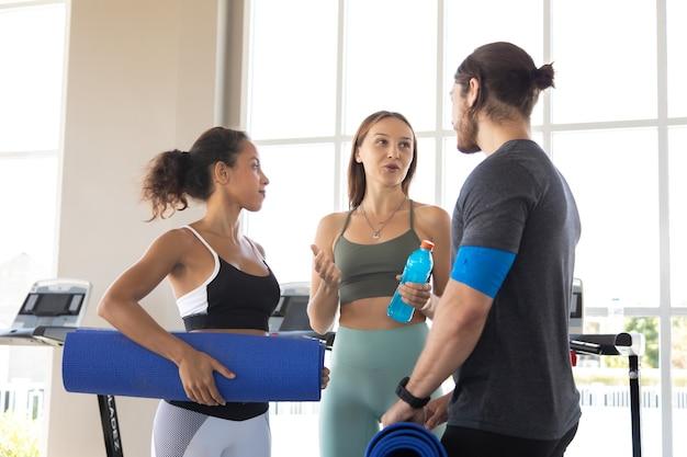 Grupo de pessoas conversando e rindo juntos depois de um treino na academia. fitness e conceito de estilo de vida saudável.