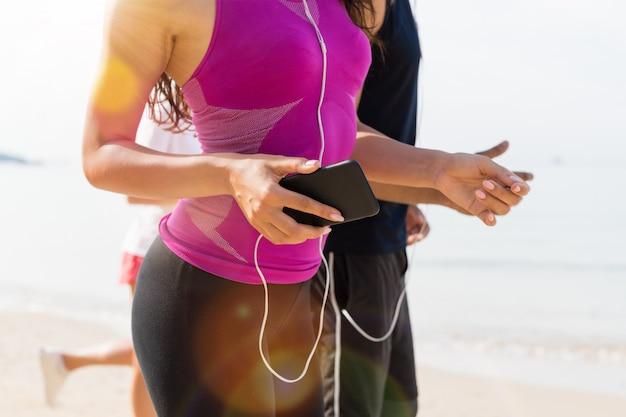 Grupo de pessoas corredores na praia closeup de jovens corredores do esporte